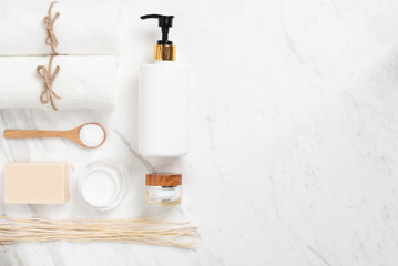 Top view of Cosmetic bottles, soap, wooden spoon and towel on white marble.