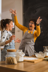 grandmother and her granddaughter baking together in kitchen