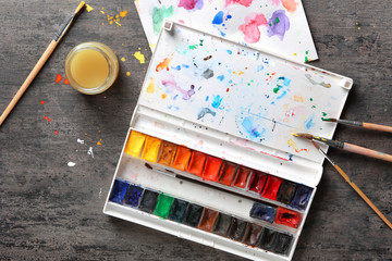 Paint palette with brushes on grey background