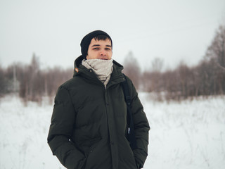 winter portrait of a man in the cold in a knitted scarf