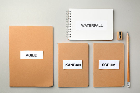 Notebooks with words AGILE, WATERFALL, KANBAN, SCRUM on light background