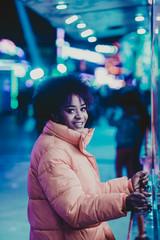 Smiling black woman playing arcade game at night