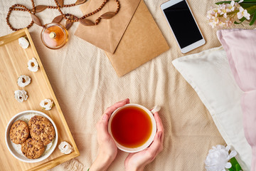 Woman holding mug of hot tea. Lazy cozy morning in bed. Flat lay woman accessories with letter, envelope, smartphone, perfume.