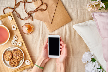 Flatlay women's hands holding a smartphone. Cozy home rest, vacation, weekend. Girl lying on the bed, around women's accessories, tea, cookies, pillows, flowers, letter.