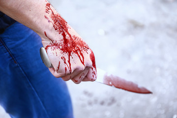 Maniac with bloodstained knife outdoors