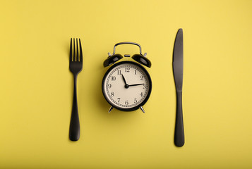 Alarm clock and cutlery on color background. Diet concept