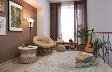 Stylish interior of living room with comfortable lounge armchair