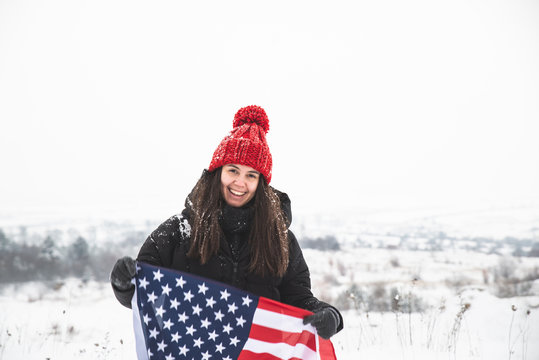 young smiling woman in red hat holding usa flag. winter time