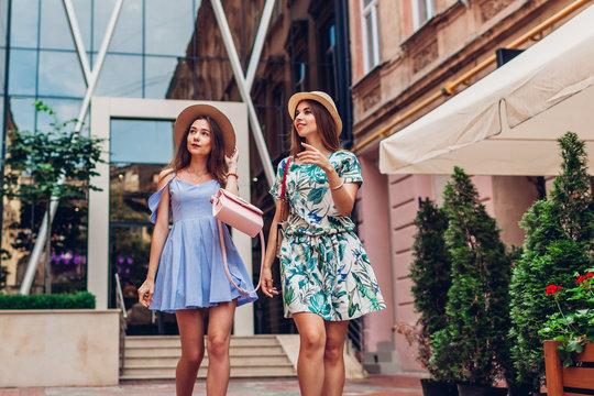 Outdoor portrait of two young beautiful women walking on city street. Best friends hanging, having fun