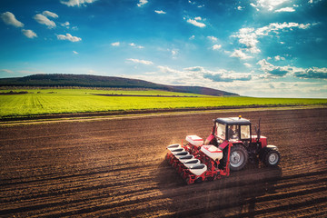 Farmer with tractor seeding crops at field, aerial drone view