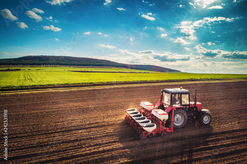 Wall mural Farmer with tractor seeding crops at field, aerial drone view