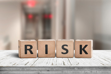 Risk sign on a wooden desk with red lights