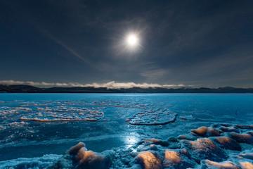 Full moon shining over blue ice surface of frozen Lake Laberge, Yukon Territory, Canada Fotoväggar