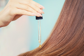 Pipette with oil to restore and protect long hair client girl