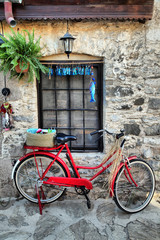 a red old bicycle against a stone wall in Old Datca street, Mugla, Turkey