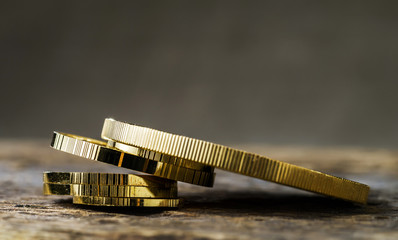 A pile of gold coins of various sizes on a neutral blurred background. Selective focus.