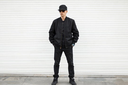Stylish young attractive man hipster in a black cap in black sunglasses in stylish jeans in trendy sneakers in a black bomber jacket stand on the street against a white metal wall. Serious guy.