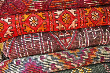 Pile of north african rugs in red, orange & brown shades, Morocco.