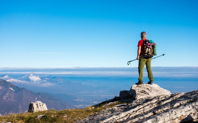 Hiker on the top in mountains. Travel sport lifestyle concept.