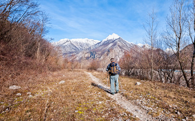 Man hiker walking on trail toward the mountains.