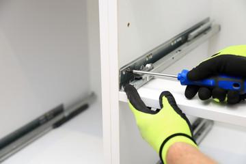 Robotnik wkręca śrubę w prowadnicy mebli.