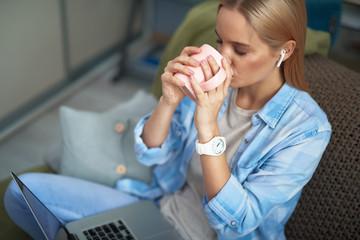 Beautiful blond girl enjoying hot drink while working on laptop
