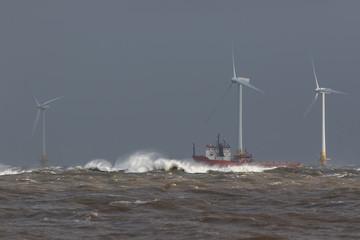 Ship sailing in rough sea around offshore wind farm turbines.
