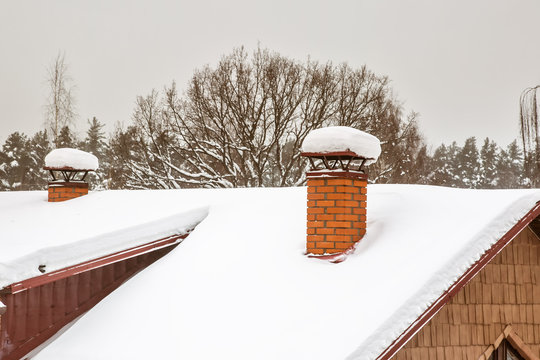 Two Red brick chimneys with iron chimney cap on the roof in snow.