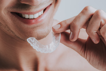 Close up of smiling man holding transparent mouth guard