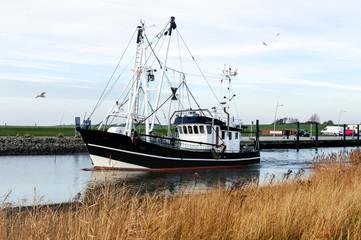 idyllischer Kutterhafen an der Nordseeküste in Wremen bei Bremerhaven, Fischkutter auf dem Weg zum Krabbenfang in in der Nordsee