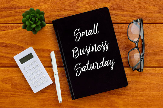 Top view of pen,calculator,eyeglasses,plant and notebook written with Small Business Saturday on wooden background. Business concept.