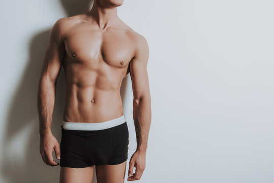 Young shirtless athletic man standing in black underwear
