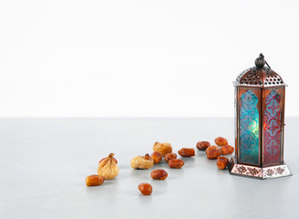 Muslim lamp and dates on table against white background. Space for text