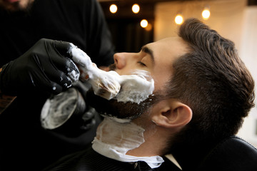 Professional hairdresser applying shaving foam onto client's skin in barbershop
