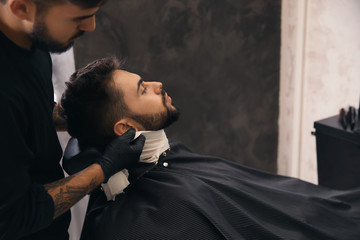 Professional hairdresser using cold towel to calm client's skin after shaving in barbershop