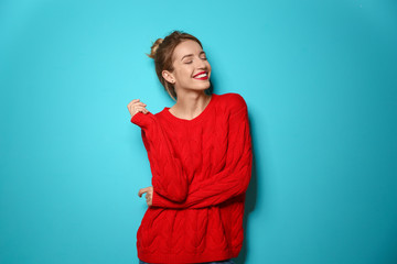 Wall Mural - Beautiful young woman in warm sweater on color background