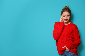 Wall Mural - Beautiful young woman in warm sweater on color background. Space for text