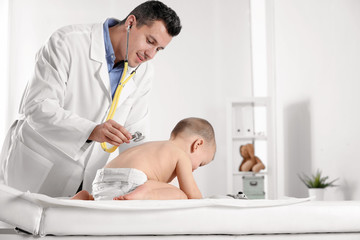 Children's doctor examining little boy with stethoscope in hospital. Space for text