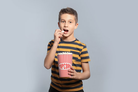 Boy with popcorn during cinema show on grey background