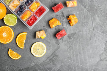 Flat lay composition with ice cube tray and fresh fruits on grey background. Space for text