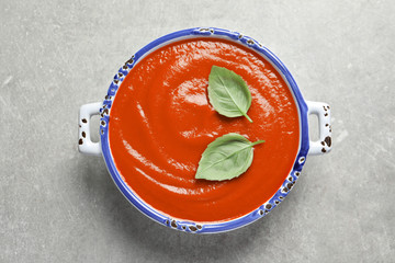 Dish with fresh homemade tomato soup on grey background, top view