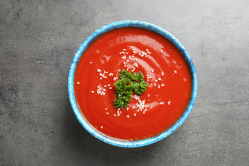 Bowl with fresh homemade tomato soup on grey background, top view