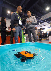 Sheng Wei Wang (R) demonstrates the Titan underwater drone, which is able to dive to 492 feet and stream video to a smartphone, at the Genuine booth during the 2019 CES in Las Vegas