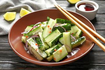 Plate with delicious cucumber salad on wooden table