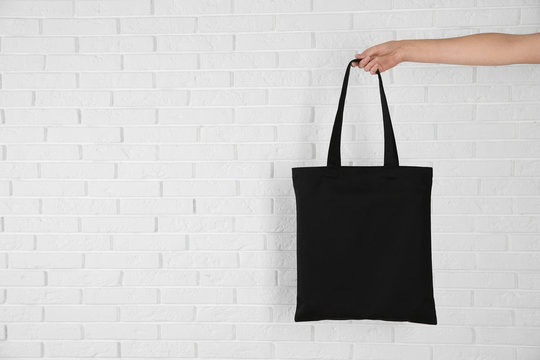 Woman holding eco bag near brick wall. Mock up for design