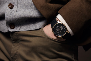 Hand in pocket with wrist watch in a stylish suit, close-up.