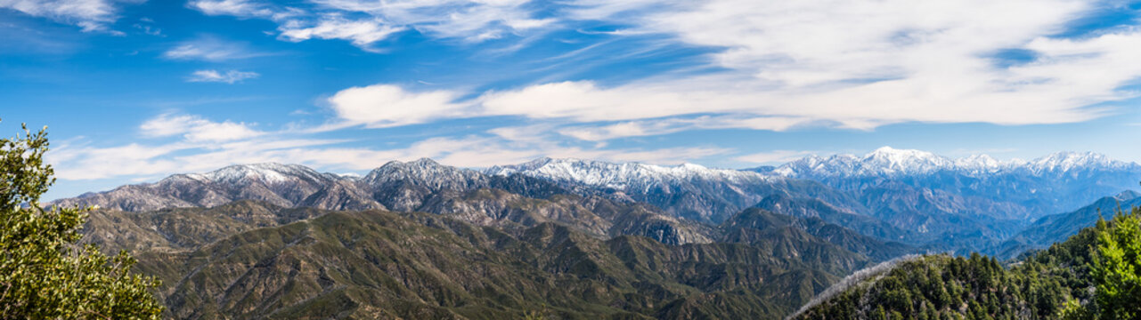 Panoramic view of Angeles National Forest on a sunny day; mountains covered in snow in the background; Los Angeles county, south California