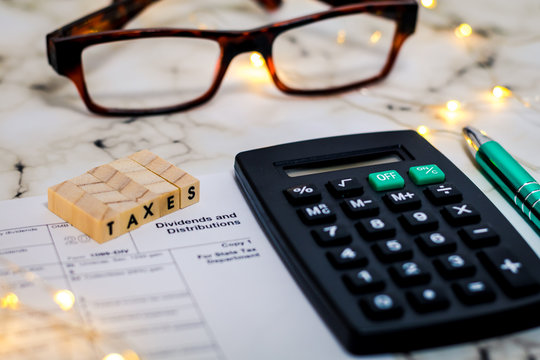 Tax still life business finance concept, form 1099, Dividends and Distributions with calculator, pen shallow DOF