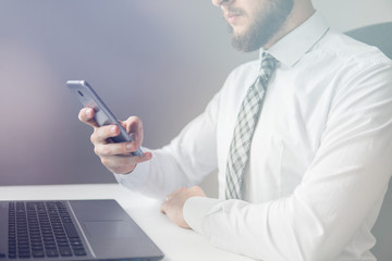 Financial business. Businessman work with computer on table in office work. Light background. Close up. Smartphone in hand Young bearded businessman. Office work with a laptop.