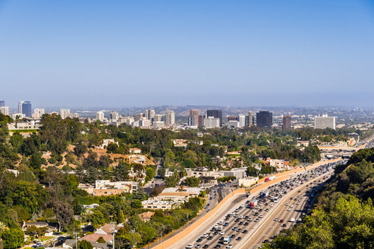 Aerial view towards the skyline of Westwood neighborhood; highway 405 with heavy traffic in the foreground; Los Angeles, California